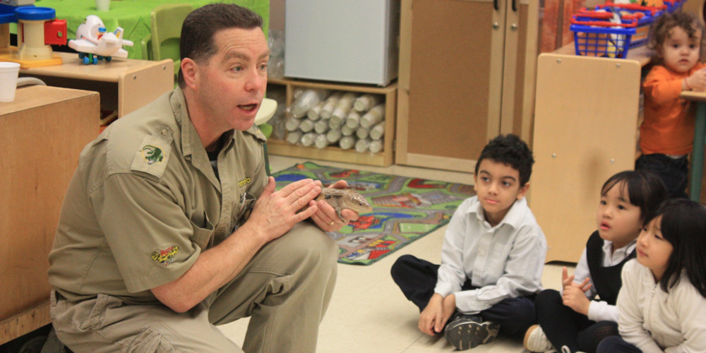 Reptilia educator teaches kids in a classroom about blue-tongued skinks